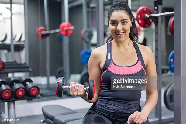Portrait of a smiling young woman at gym holding dumbbell