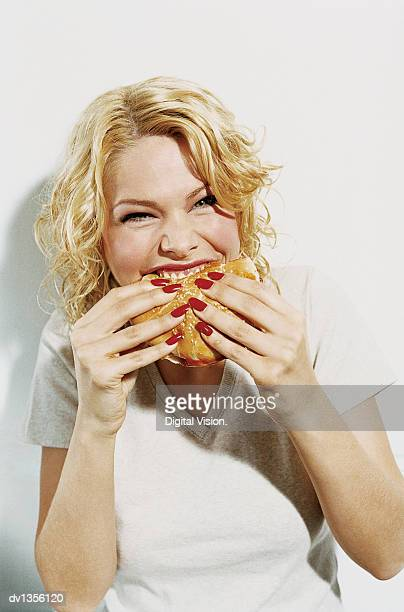 Portrait of a Smiling, Young Woman Eating a Hamburger