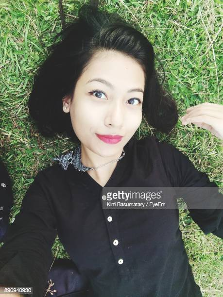 Portrait Of A Smiling Young Woman Lying Down On Grass