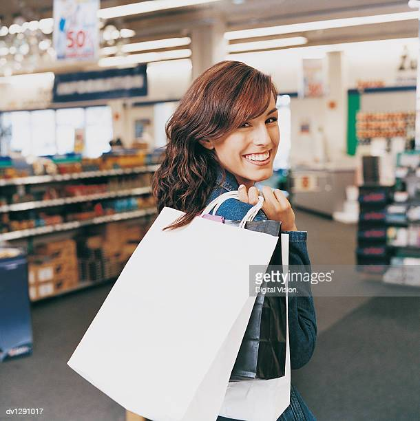 Portrait of a Smiling, Young Woman Standing in a Department Store Holding Shopping Bags
