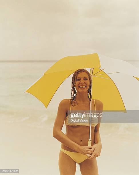 Portrait of a Smiling, Young Woman Standing on a Beach With An Umbrella in a Bikini on a Rainy Day