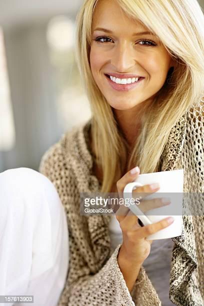 Ritratto di un sorridente giovane donna con una tazza di caffè