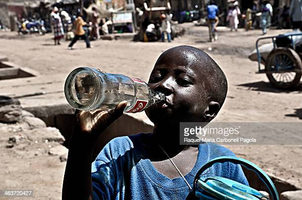 Portrait of a street child drinking CocaCola