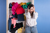 Portrait Of A Stressed Young Woman In Front Of Scattered Clothes On Shelf