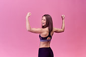 Portrait of a strong beautiful woman from behind with muscles and happy joyful emotion. The athlete shows off her impressive biceps in her hands and is proud of the goal achieved