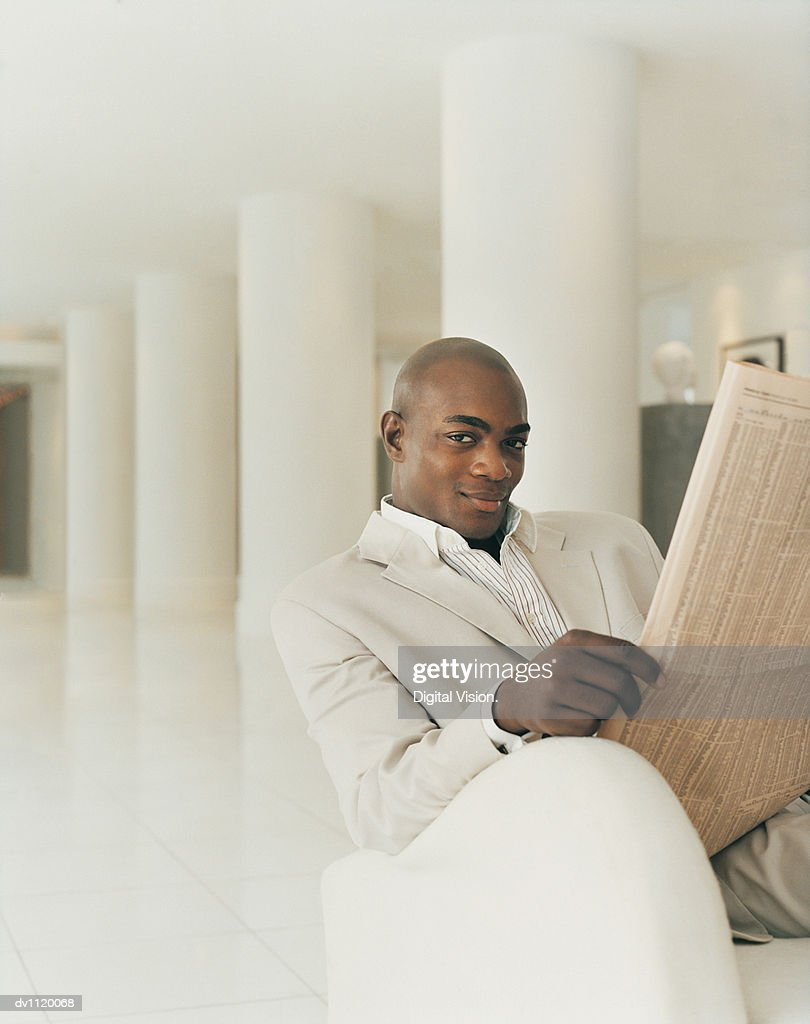 Portrait of a Stylish Businessman Sitting in a Hotel Lobby Holding a Newspaper : Stock Photo