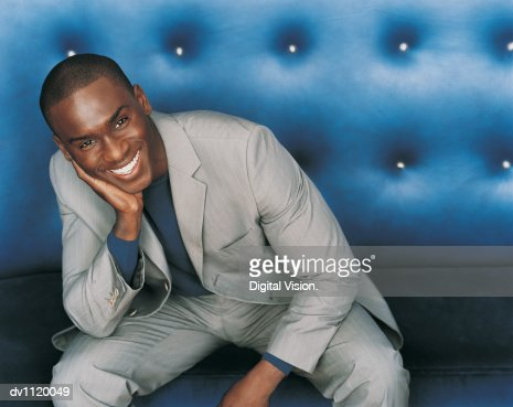 Portrait of a Stylish Businessman Sitting on a Blue Seat : Stock Photo