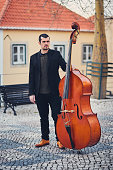 Portrait of a stylish man with a beard on an old street with a double bass. A solid musician with a large musical instrument in brown leather shoes, a shirt and a jacket on the European square