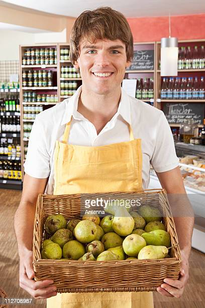 Portrait of a supermarket sales clerk holding a basket of pears