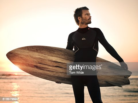 Portrait of a surfer holding a wooden surf board