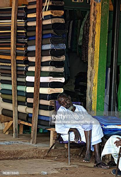 Portrait of a tailor sleeping at his textile store´s doorway