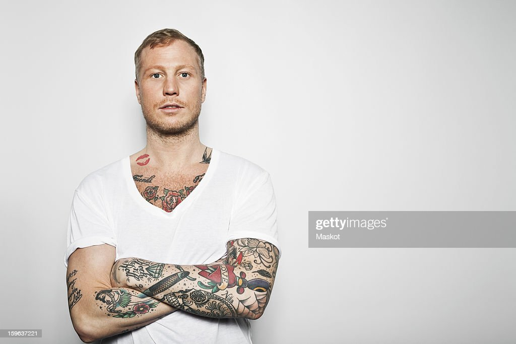 Portrait of a tattooed man with arms crossed standing against grey background