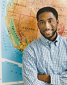 Portrait of a Teacher Standing by a Map of the USA in a Classroom