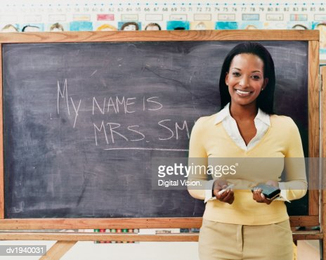 Portrait of a Teacher Standing Next to a Blackboard in a Classroom : Stock Photo