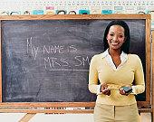 Portrait of a Teacher Standing Next to a Blackboard in a Classroom