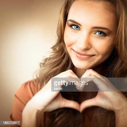 Portrait of a teen girl making a heart shape with her hands