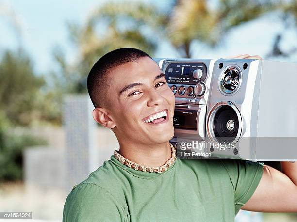 Portrait of a Teenage Boy Carrying a Portable Stereo on His Shoulder and Laughing