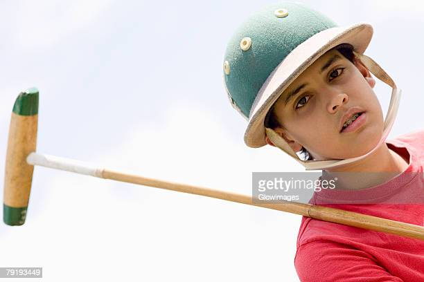 Portrait of a teenage boy holding a polo mallet