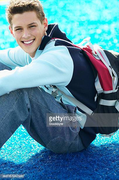 portrait of a teenage boy (16 - 18) sitting on a football field