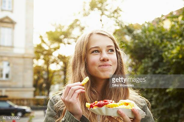 portrait of a teenage girl eating french fries