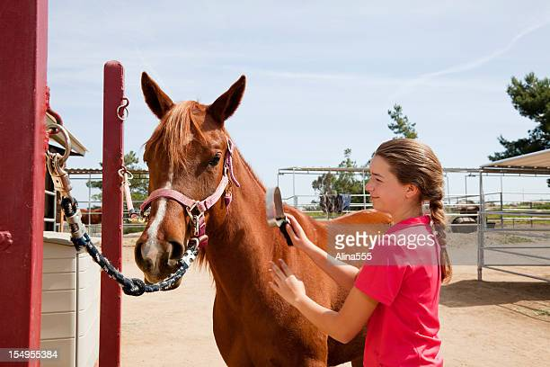 Portrait of a teenage girl grooming her horse