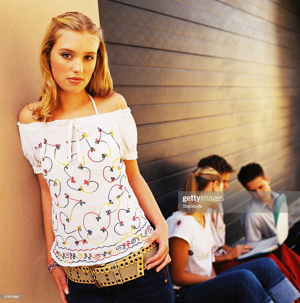 Portrait of a teenage girl standing against a wall with a group of teenagers (16-20) behind her : Stock Photo