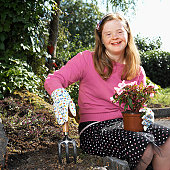 portrait of a teenage girl (14-17) with down syndrome gardening