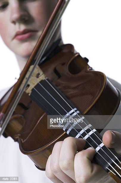 portrait of a teenage male as he holds up and practices his violin