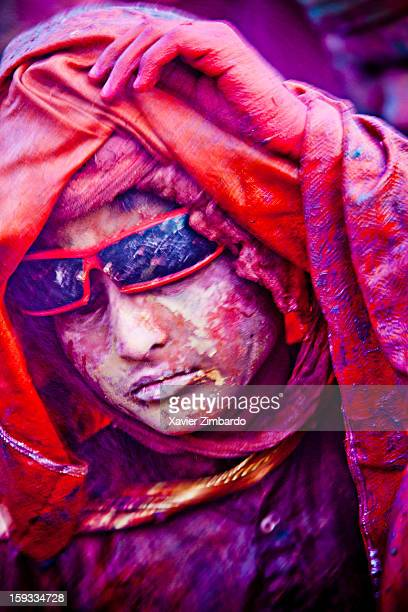 Portrait of a teenager covered with coloured powdered dye and coloured water that people throw on each other during Holi the merriest of all the...