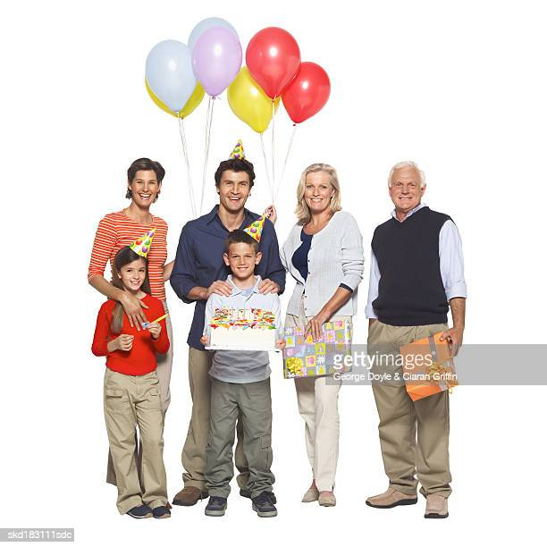 Portrait of a three generation family holding balloons and gifts and a birthday cake
