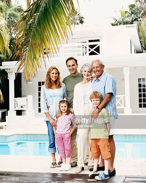 Portrait of a Three Generational Family With a Young Boy and Girl Standing by a Seimming Pool