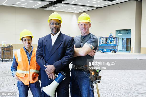 Portrait of a Three Smiling People Wearing Hard Hats in an Incomplete Room