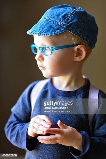 Portrait of a toddler child wearing a denim cap and eyeglass frames