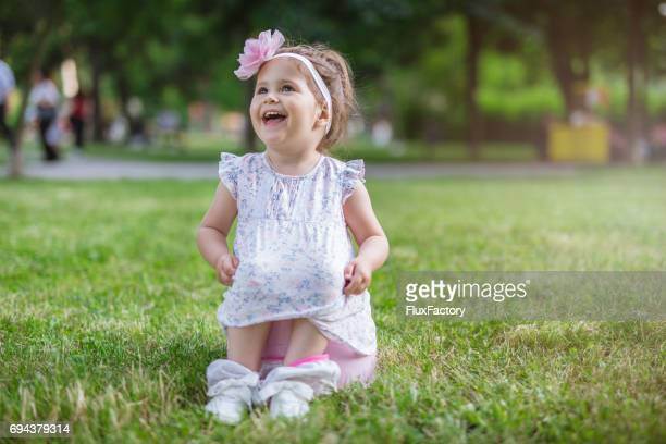 Portrait of a toddler girl laughing on a potty