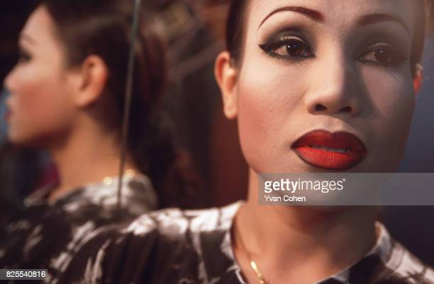 A portrait of a transsexual performer fully madeup as she prepares to go on stage for a show at a night club in the Silom area of downtown Bangkok