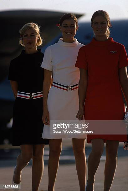Portrait of a trio of American Airlines air stewardesses as they pose in uniform on an airport tarmac September 1967 The photo was taken as part of a...