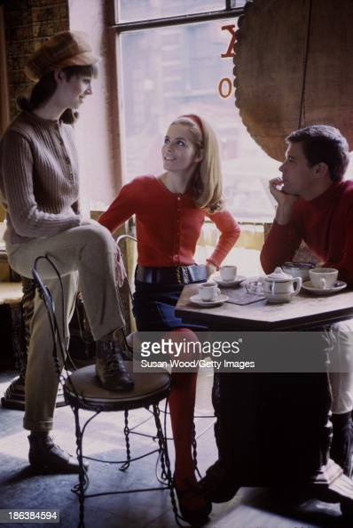 Portrait of a trio of models two women and one man as they pose in a Soho coffeeshop for a fashion shoot New York New York May 1966 One woman wears a...