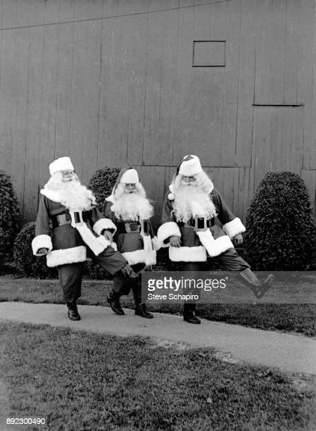Portrait of a trio of unidentified men all dressed in Santa Claus costumes as they kick their legs on a pathway Albion New York 1964