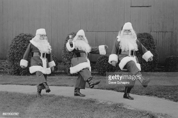 Portrait of a trio of unidentified men all dressed in Santa Claus costumes and one with a bell as they kick their legs on a pathway Albion New York...