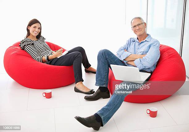 Portrait of a two office workers relaxing on bean bags