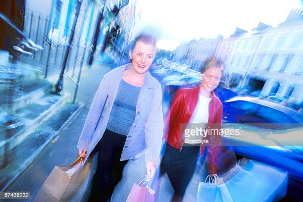 portrait of a two young women walking with shopping bags