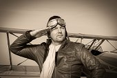 Portrait of a vintage pilot with leather cap, scarf and aviator glasses in front of a historic airplane biplane - Portrait of a man in historical pilot clothing - vintage old picture style