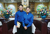 Portrait of a waiter and a waiter standing in a restaurant