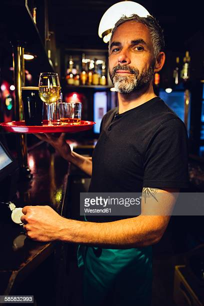 Portrait of a waiter holding tray in an Irish pub