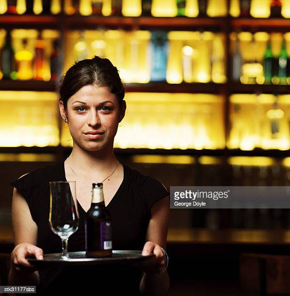 portrait of a waitress holding a tray with a bottle of beer and a glass on it