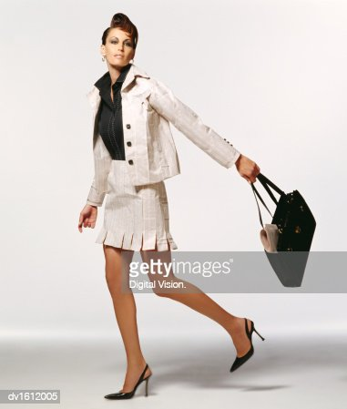 Portrait of a Well Dressed Woman Wearing Clothes made from Paper and Swinging a Handbag : Stock Photo