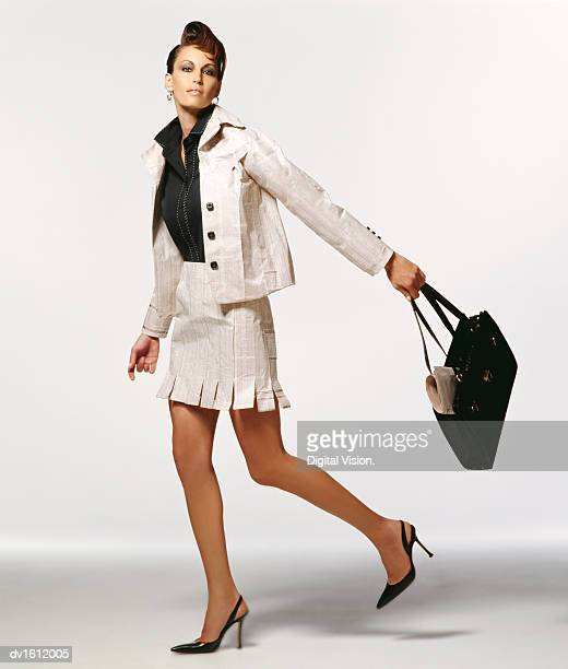 Portrait of a Well Dressed Woman Wearing Clothes made from Paper and Swinging a Handbag