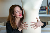 Portrait of a woman 48 years old, smiling and embracing a mannequin looking at camera at home.