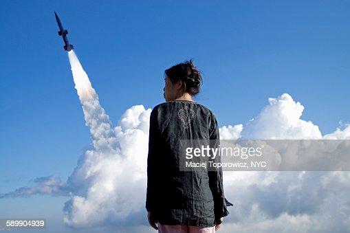 Portrait of a woman against rocket launch