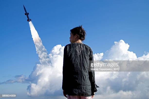 Portrait of a woman against rocket launch